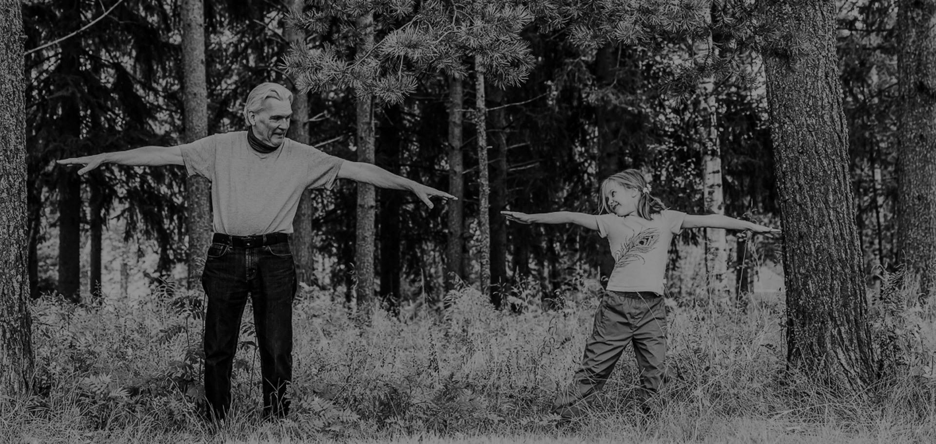 Bestefar og barnebarn står ved siden av hverandre og strekker armene ut mot hverandre